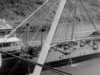 1934 B/W MONTAGE MS HA WS Ocean liner passing through Panama Canal, Freight ship passing by, officer standing on ship's bridge looking at view, jungle trees through open portholes  / Panama Canal, Panama