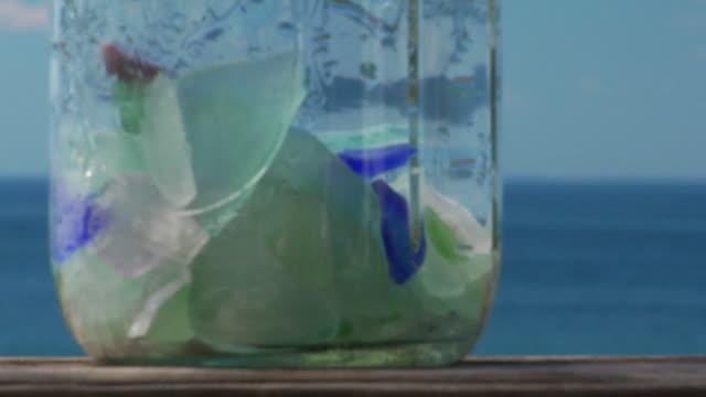 ECU, R/F, ocean shells in jar, ocean in background, North Truro, Massachusetts, USA