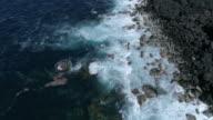 Ocean surge on black lave coastline, top down aerial