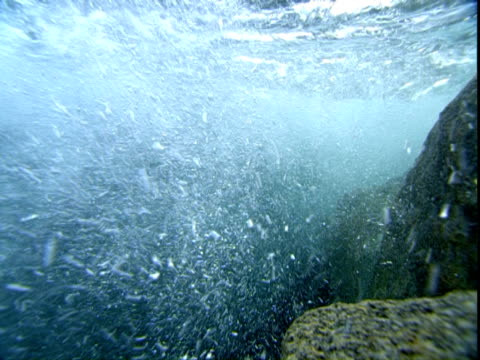 Ocean water churns as it moves over rocks near the surface.