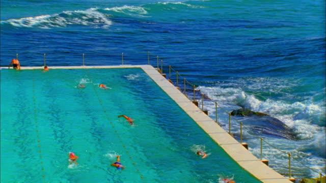 Slo Mo Ws Ha Ocean Wave Splashing Over Edge Of Salt Water Pools With Swimmers Swimming At Bondi