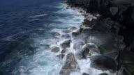 Ocean waves breaking on black lava coast, slow motion aerial