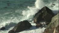Ocean waves crash against large rocks.
