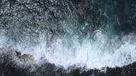 Ocean waves rolling on black lava coast, top down slow motion aerial