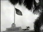Oceanside building flying United States flag / car pulling up to large white villa / guard saluting car / Sawyer and other men looking at map in...