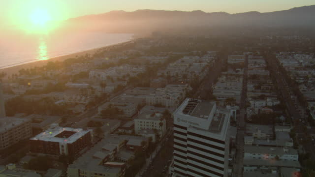 AERIAL Oceanside city during sunset with mountains in the distance / United States