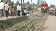 October 15 2010 WS Train moving slowly towards town as passengers walk across tracks and onto platform / Mozambique Africa