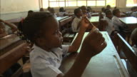 October 19 2010 PAN Elementary school students sitting at their desks holding a length of string as their teacher instructs them / Mozambique