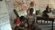 October 19 2010 PAN Teacher swaying with drummers while students dance and sing in classroom / Mozambique