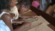 October 20 2010 TU Students drawing at desks laughing and chattering and teacher at front of classroom / Mozambique