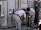 October 2004 / UN workers unlocking doors to cargo container on truck containing ballot boxes at Kandahar Stadium as ballots start to arrive in days...
