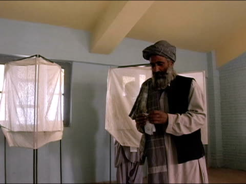 October 9 2004 Man leaving voting booth with ballot / placing slip in box stuffed with ballots / tilt down to medium shot of ballot box / Kandahar...