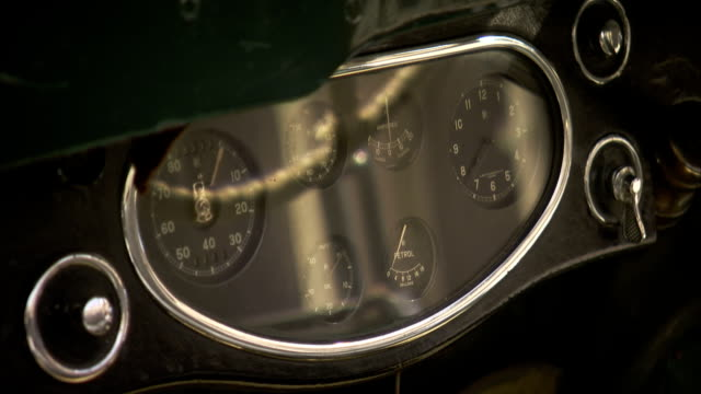 Odometers and switches cover the dash board of a classic car.