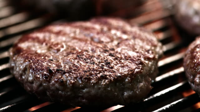 SLO MO LD of beef burger sizzling on a grill