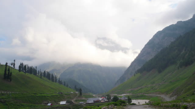 TL of clouds engulfing the higher snow covered peaks as seen from Sonamarg in Kashmir