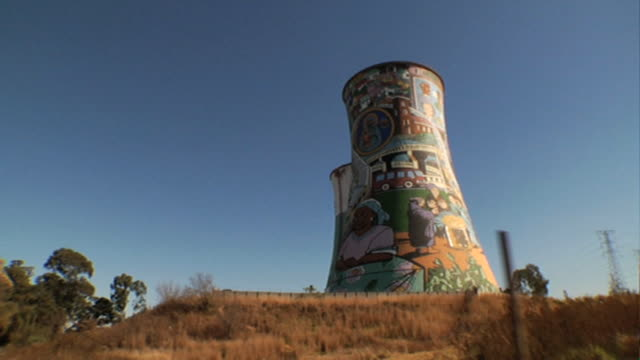 DRIVEBY of power plant cooling towers one entirely covered w/ graffiti art