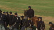 Of unidentifiable Union Army soldier reenactors walking in infantry platoon w/ officer on horseback on field PA Battle of Gettysburg soldiers