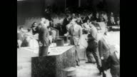 INT of United Nations meeting room with representatives seating in their seats looking towards three seated men on center podium / individual members...