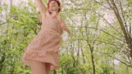 SLO MO 4K of woman twirling under the falling petals