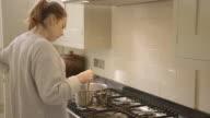 M/W of Women cooking in modern kitchen