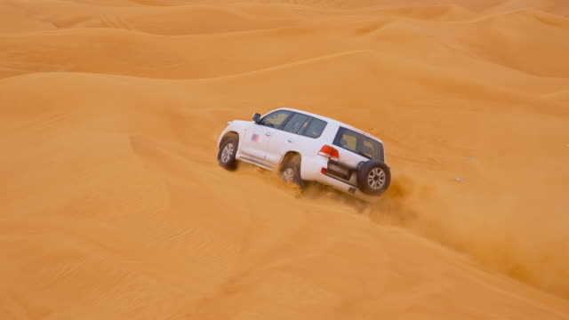 SLO MO Off road car driving over a sand dune
