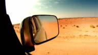 Off road in desert in Africa. Car mirror close-up.