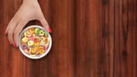 Offering multicolored cereal rings with milk