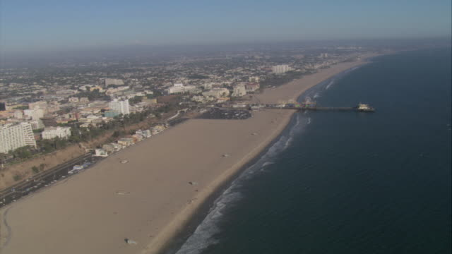 AERIAL Office buildings approaching the beach and the ocean / Santa Monica, California, United States