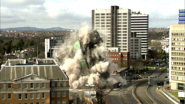 WS   Office builing is demolished in controlled implosion with  explosives and huge dust cloud rises up  / Birmingham, West Midlands, UK