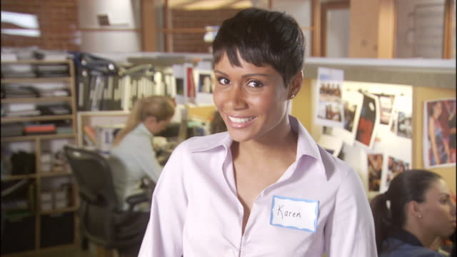 CU Office worker wearing name tag and smiling in office / Los Angeles, California, USA