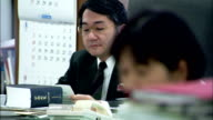 Office workers in an open-plan office, Japan. Available in HD.