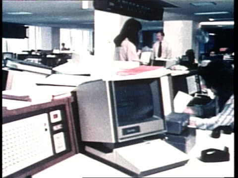 Office workers sit at desks in front of computers