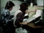 1979 MONTAGE Office workers using paper documents to record information / United States