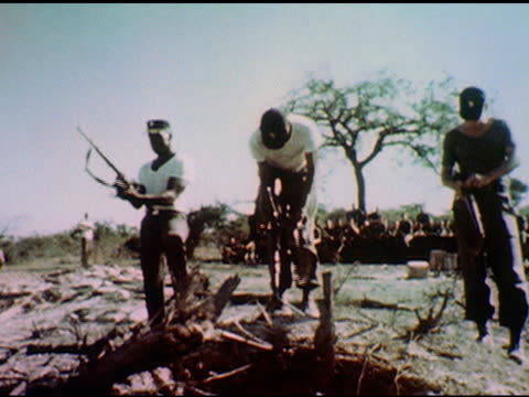 / Officer addresses group of seated soldiers / Three soldiers load guns one automatic / Shot from behind as they fire guns into empty landscape on...
