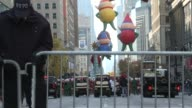 NYPD officer puts up a barricade to seal off pedestrian traffic from the end of the parade / Crowds fill space where parade has vacated / Rear view...