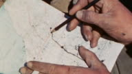 Officer's hands drawing battle lines on map and map with lines / Iwo Jima Japan
