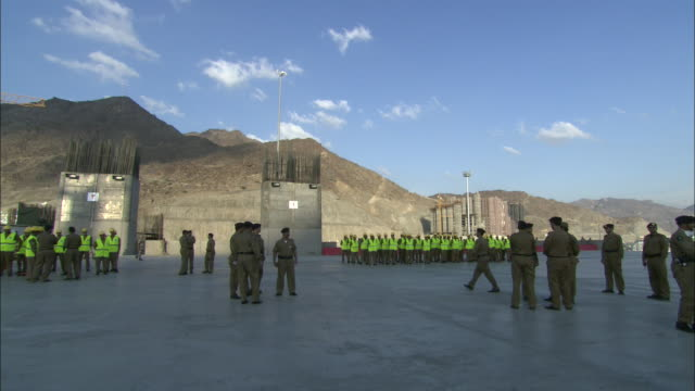 Officers speak together and walk around a military base near a platoon of soldiers.
