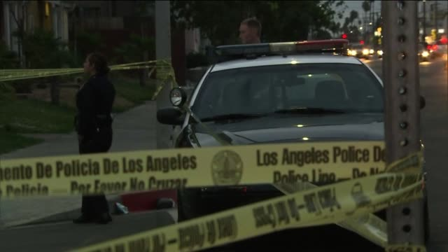 Officers Stand Behind Police Tape and Investigate Shooting on September 03 2013 in Los Angeles California