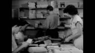 Offices of National Committee on Atomic Information w/ people preparing mailings 'stuffing envelopes' CU EXT Atomic information brochures pamphlets...