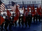Officials in stands stand and salute / Marines march in formation in street with flags
