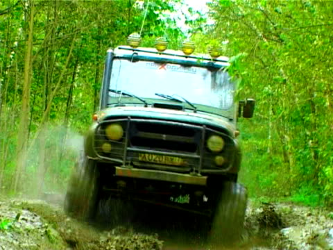 Offroad racing. Jeep driving through the wet forest