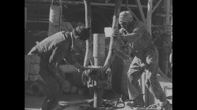 Oil derrick crane lowering 'collar' inside derrick / Oil workers attaching equipment like collar on oil well piping / Crane pulling oil pipe up oil...