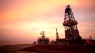 oil drill platform sailing in sunset