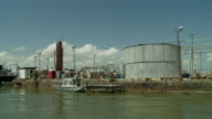 Oil storage tanks, boats and other equipment line a riverbank in New Orleans.