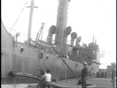 1923 WS Oil tanker docked while longshoremen are loading a large hose onto deck / United States