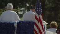 Old American legion veterans with USA flag wave in a parade in a small town.