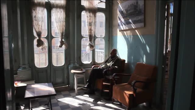 MS Old arab man drinking tea and near beautiful sun lit window. / Amman, Jordan