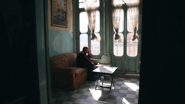 MS Old arab man drinking tea and smoking near  beautiful sun lit window / Amman, Jordan
