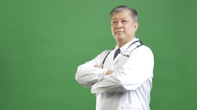 old Asian man doctor in white uniform poses at camera 4k