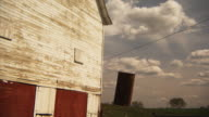 MS Old barn with leaning silo in rural landscape, Iowa, USA